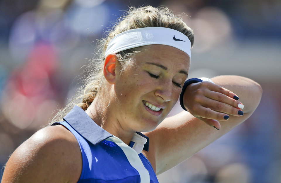Photo - Victoria Azarenka, of Belarus, wipes sweat from her brow between points against Ekaterina Makarova, of Russia, during the quarterfinals of the 2014 U.S. Open tennis tournament, Wednesday, Sept. 3, 2014, in New York. (AP Photo/Mike Groll)