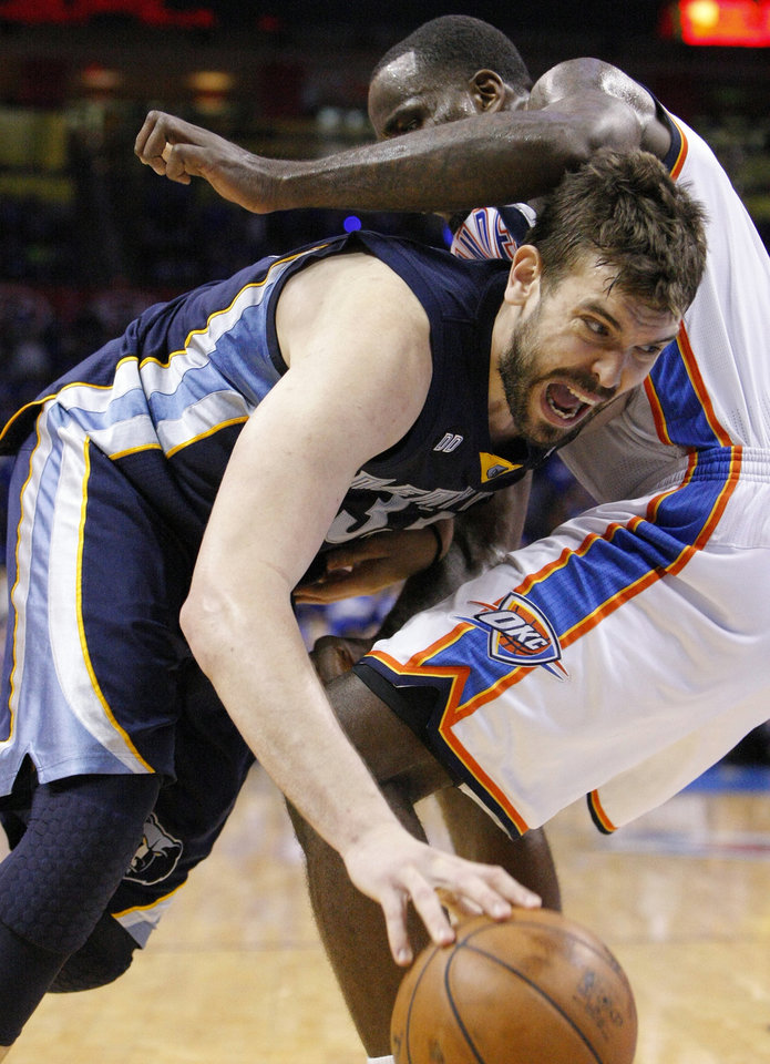 Photo - Memphis Grizzlies Marc Gasol, left, drives to the basket as Oklahoma City Thunder's Kendrick Perkins defends during the fourth quarter of Game 1 of their NBA basketball playoff series in the Western Conference semifinals, Sunday, May 5, 2013, in Oklahoma City. Oklahoma City won 93-91. (AP Photo/Alonzo Adams)