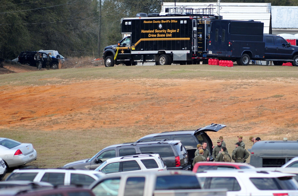 Photo - Federal and local law enforcement officers gather at their trucks after the hostage crisis ended in Midland City, Ala., on Monday afternoon, Feb. 4, 2013.  Officials say they stormed a bunker in Alabama to rescue a 5-year-old child being held hostage there after his abductor was seen with a gun. (AP Photo/The Dothan Eagle, Jay Hare)