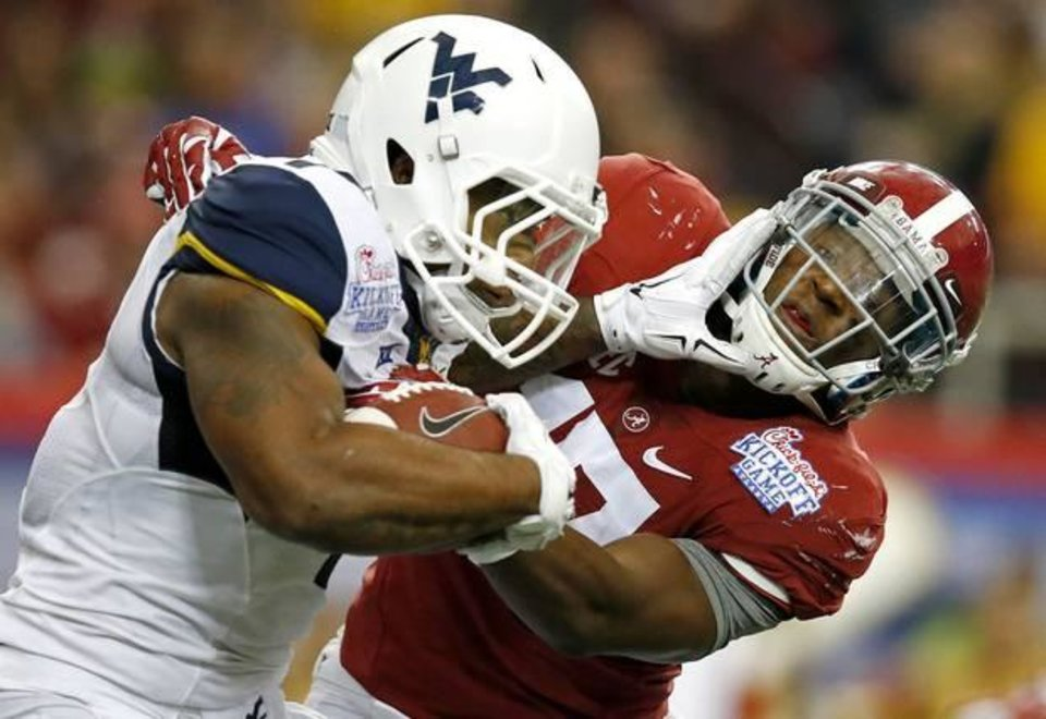 Photo -  West Virginia's Rushel Shell fights off Alabama's Kenyan Drake during a punt return Saturday. Bama beat the Mountaineers 33-23, but West Virginia gained a ton of respect for the Big 12. (AP Photo)