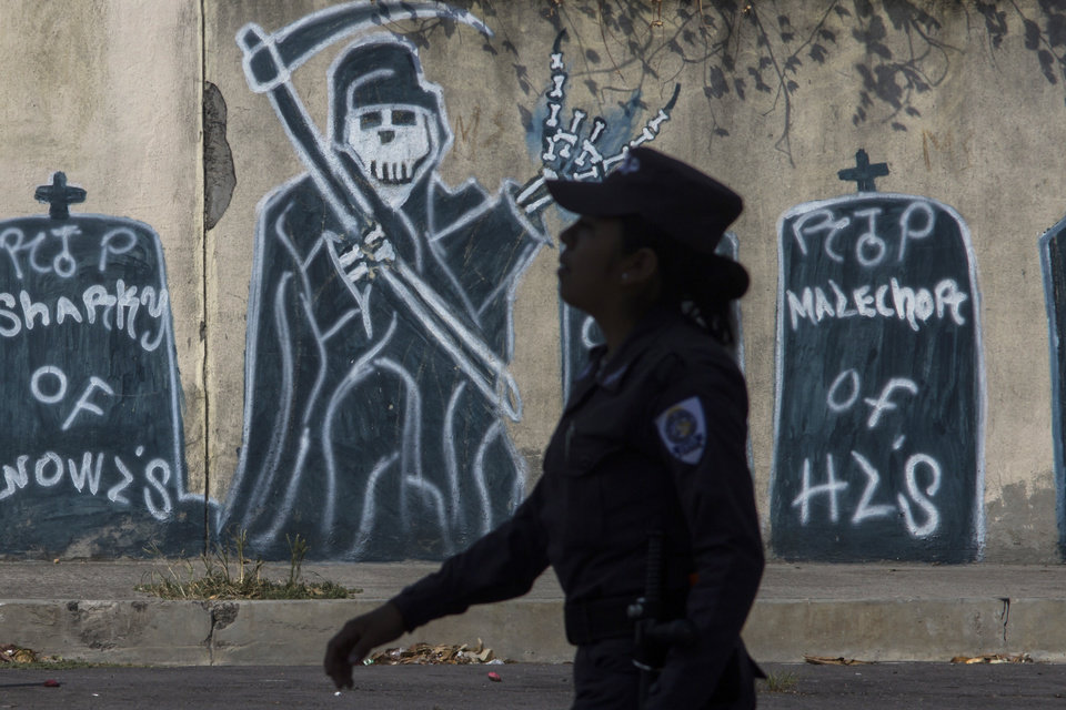 Photo - FILE - In this April 14, 2014 file photo, a police officer walks past graffiti depicting gang members that have died during a patrol in a neighborhood controlled by the Mara Salvatrucha gang in Ilopango, El Salvador. In El Salvador, the end of a truce between street gangs has led to a steep rise in homicides this year adding impetus to the migration of youths and children to the U.S.  (AP Photo/Salvador Melendez, File)