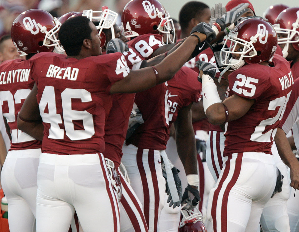 Photo - D.J. Wolfe (25) is greeted by his teammates after an interception against Missouri during the first half of the college football game between  the University of Oklahoma Sooners (OU) and the University of Missouri Tigers (MU) at the Gaylord Family Oklahoma Memorial Stadium on Saturday, Oct. 13, 2007, in Norman, Okla. By STEVE GOOCH, The Oklahoman