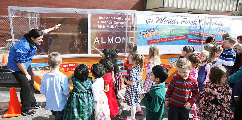 Sarah Lynn Brannan, left shows students at Windsor Hills Baptist School the world's largest chocolate bar in Oklahoma City, Monday, February  20,  2012. The children were learning about eating in moderation. Photo By Steve Gooch, The Oklahoman