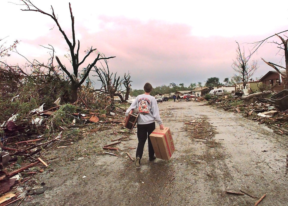 MAY 3, 1999 TORNADO: Tornado damage, victims: Norma Musgrave carries boxes down a storm ravaged street in Midwest City to a friend's house that was destroyed in Monday night's tornado.  Musgrave lives in Moore and her home escaped damage by less than a mile.