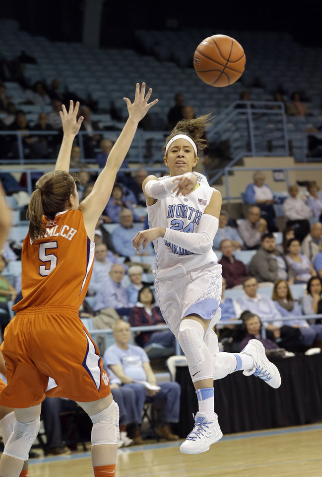 Photo - North Carolina's Jessica Washington, right, passes as Clemson's Kelly Gramlich (5) defends during the first half of an NCAA college basketball game in Chapel Hill, N.C., Thursday, Jan. 16, 2014. (AP Photo/Gerry Broome)