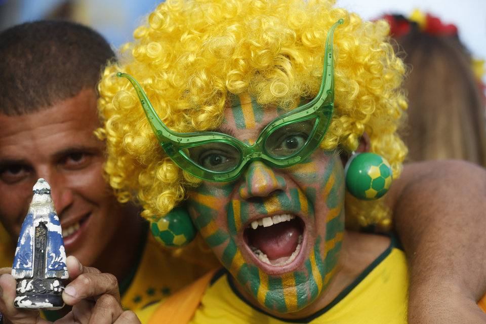 Photo - A Brazil soccer fan in costume reacts to the camera as he waits for the start of the World Cup soccer game between Brazil and Croatia inside the FIFA Fan fest area on Copacabana beach in Rio de Janeiro, Brazil, Thursday, June 12, 2014. (AP Photo/Silvia Izquierdo)