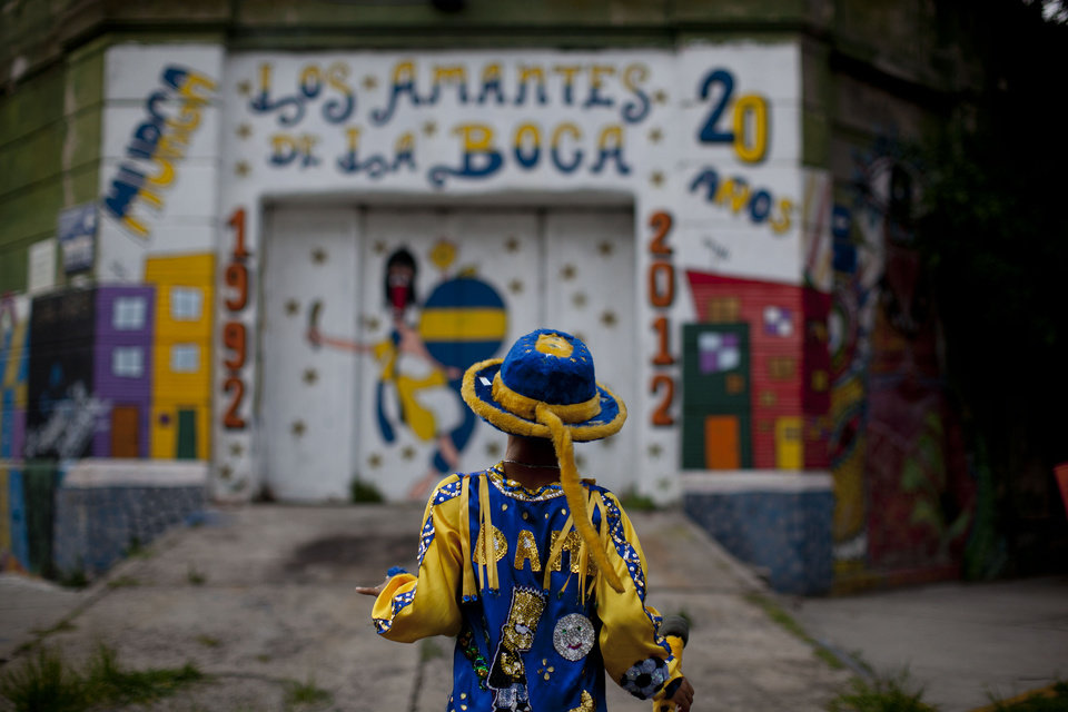 "Damian Carballo, a member of the murga ""Los amantes de La Boca,"" walks at the La Boca neighborhood before participating in carnival celebrations in Buenos Aires, Argentina, Saturday, Feb. 2, 2013.  Argentina's carnival celebrations may not be as well-known as the ones in neighboring Uruguay and Brazil, but residents of the nation's capital are equally passionate about their ""murgas,"" or traditional musical troupes. The murga ""Los amantes de La Boca,"" or ""The Lovers of The Boca"" is among the largest, with about 400 members. It's a reference to the hometown Boca Juniors, among the most popular soccer teams in Argentina and the world. (AP Photo/Natacha Pisarenko)"