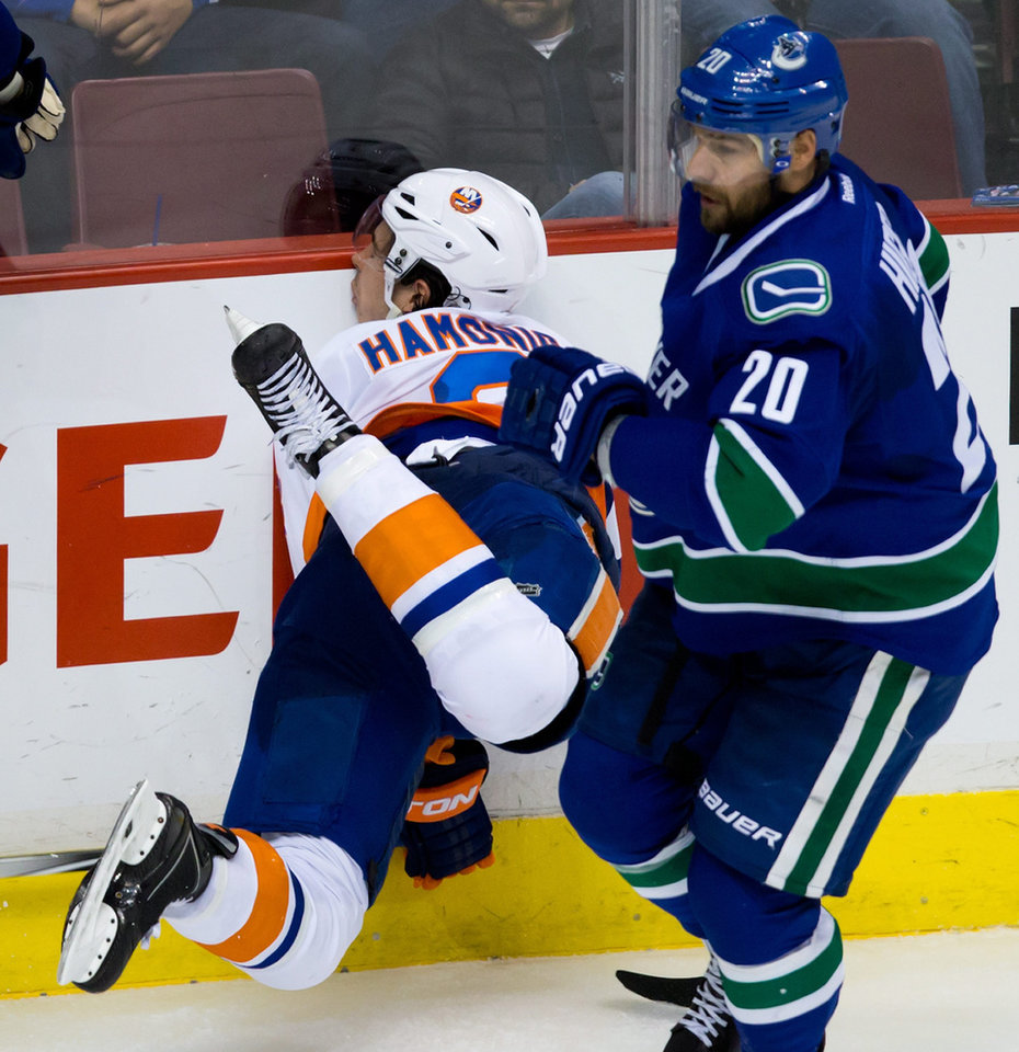 Photo - New York Islanders' Travis Hamonic, left, is checked into the boards by Vancouver Canucks' Ryan Kesler as Chris Higgins, right, skates past during third period NHL hockey action in Vancouver, British Columbia, on Monday March 10, 2014. (AP Photo/The Canadian Press, Darryl Dyck)