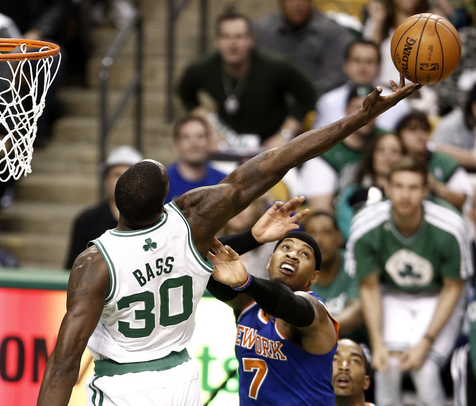 Photo - Boston Celtics' Brandon Bass (30) tries to get a rebound over New York Knicks' Carmelo Anthony during the second quarter of Game 3 of a first-round NBA basketball playoff series in Boston, Friday, April 26, 2013. (AP Photo/Winslow Townson)