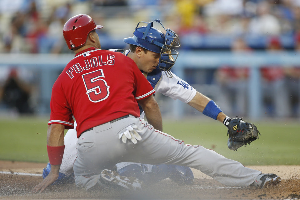 Photo - Los Angeles Dodgers' catcher A.J. Ellis tags out Los Angeles Angels' Albert Pujols at home plate during the first nning of a baseball game, Monday, August 4, 2014, in Los Angeles. (AP Photo/Danny Moloshok)