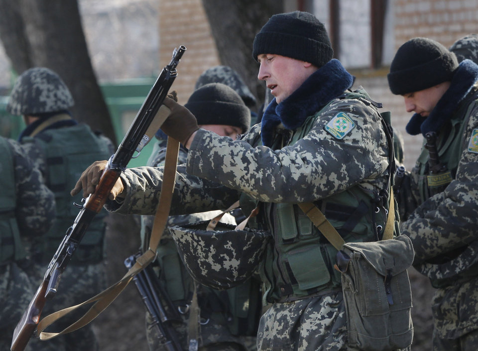 Photo - Ukrainian border guards prepare for training at a military camp in the village of Alekseyevka on the Ukrainian-Russian border, eastern Ukraine, Friday, March 21, 2014. Russian President Vladimir Putin has signed a resolution approved by parliament to annex Crimea. (AP Photo/Sergei Grits)