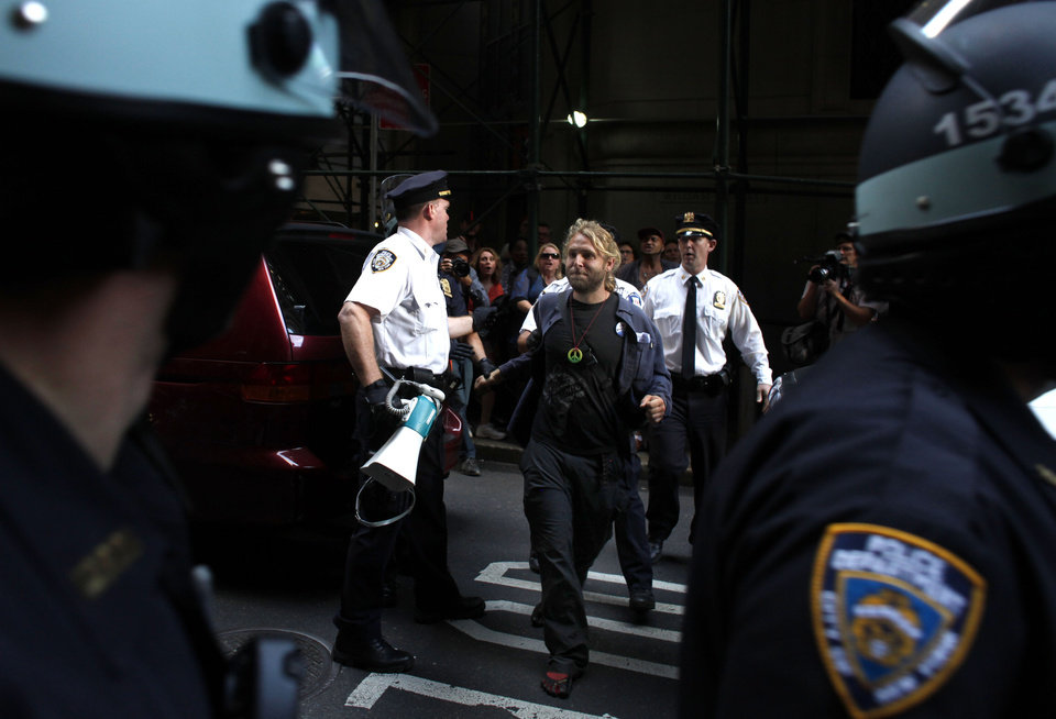 Photo -   A man is led away during an Occupy Wall Street march, Monday, Sept. 17, 2012, in New York. A handful of Occupy Wall Street protestors were arrested during a march on the New York Stock Exchange on the anniversary of the grass-roots movement. (AP Photo/Jason DeCrow)