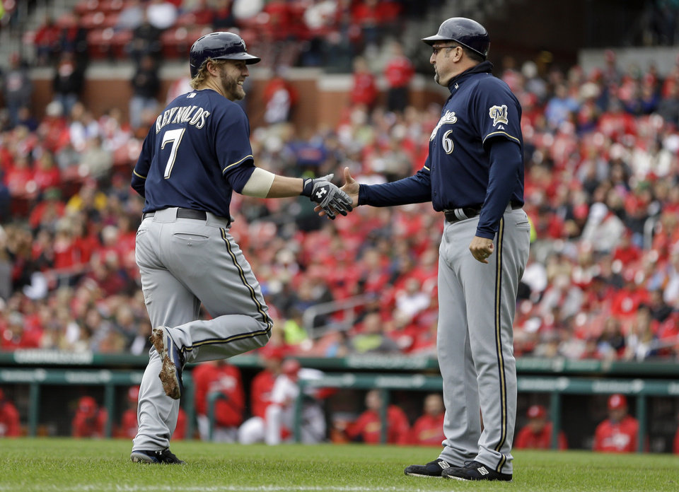 Photo - Milwaukee Brewers' Mark Reynolds, left, is congratulated by third base coach Ed Sedar while rounding the bases after hitting a two-run home run during the second inning of a baseball game against the St. Louis Cardinals Wednesday, April 30, 2014, in St. Louis. (AP Photo/Jeff Roberson)