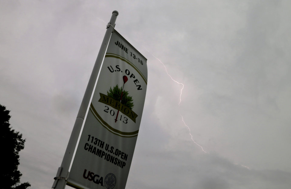 Photo - Lightning flashes in the sky as a weather warning delays the first round of the U.S. Open golf tournament at Merion Golf Club, Thursday, June 13, 2013, in Ardmore, Pa. (AP Photo/Morry Gash)