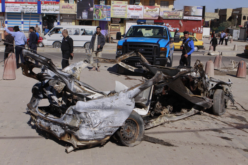 Iraqi security forces inspect the scene of a car bomb attack in the Shiite stronghold of Sadr City, Baghdad, Iraq, Tuesday, March 19, 2013. Insurgents unleashed deadly attacks Tuesday against Shiite areas of Baghdad, killing and wounding scores of people, police said. (AP Photo/ Karim Kadim)