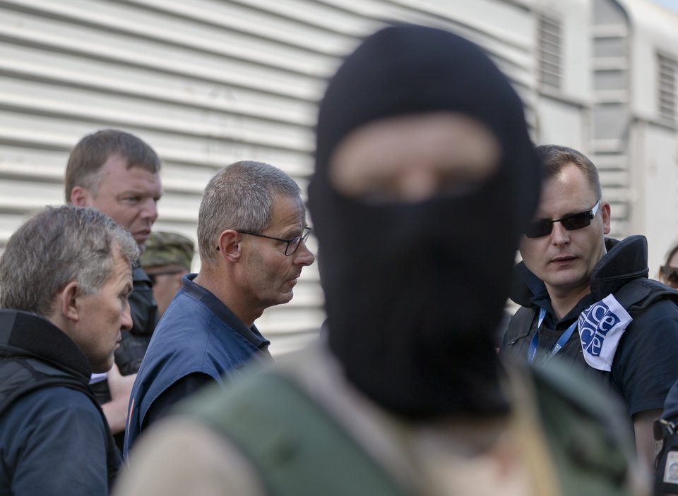 Photo - A masked pro-Russian rebel stands as Peter Van Vilet, center left, team leader of Netherlands' National Forensic Investigations Team speaks to members of the OSCE's mission to Ukraine, while inspecting a refrigerated train loaded with the bodies of passengers in Torez, eastern Ukraine, 15 kilometers (9 miles) from  the crash site of Malaysia Airlines Flight 17, Monday, July 21, 2014. Another 21 bodies have been found in the sprawling fields of east Ukraine where Malaysia Airlines Flight 17 was downed last week, killing all 298 people aboard. (AP Photo/Vadim Ghirda)