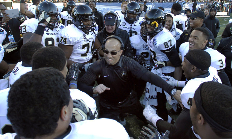 Photo - FILE - In this Saturday, Jan. 4, 2014 file photo, Vanderbilt coach James Franklin celebrates with team during the second half of the BBVA Compass Bowl NCAA college football game against Houston in Birmingham, Ala. Franklin hopped back and forth from college to NFL jobs before spending 2008-2010 as Maryland's offensive coordinator and head-coach-in-waiting. Vanderbilt hired him for the 2011 season. Three winning campaigns later, he landed one of the most prestigious jobs in college sports - head coach of Penn State's football team. (AP Photo/Butch Dill)