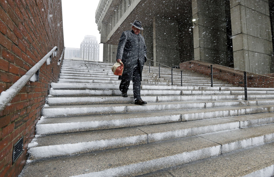 A man walks down the steps of Boston City Hall as snow falls on Friday, Feb. 8, 2013. A major winter storm is heading toward the U.S. Northeast with up to 2 feet of snow expected for a Boston-area region that has seen mostly bare ground this winter. (AP Photo/Elise Amendola) ORG XMIT: MAEA106
