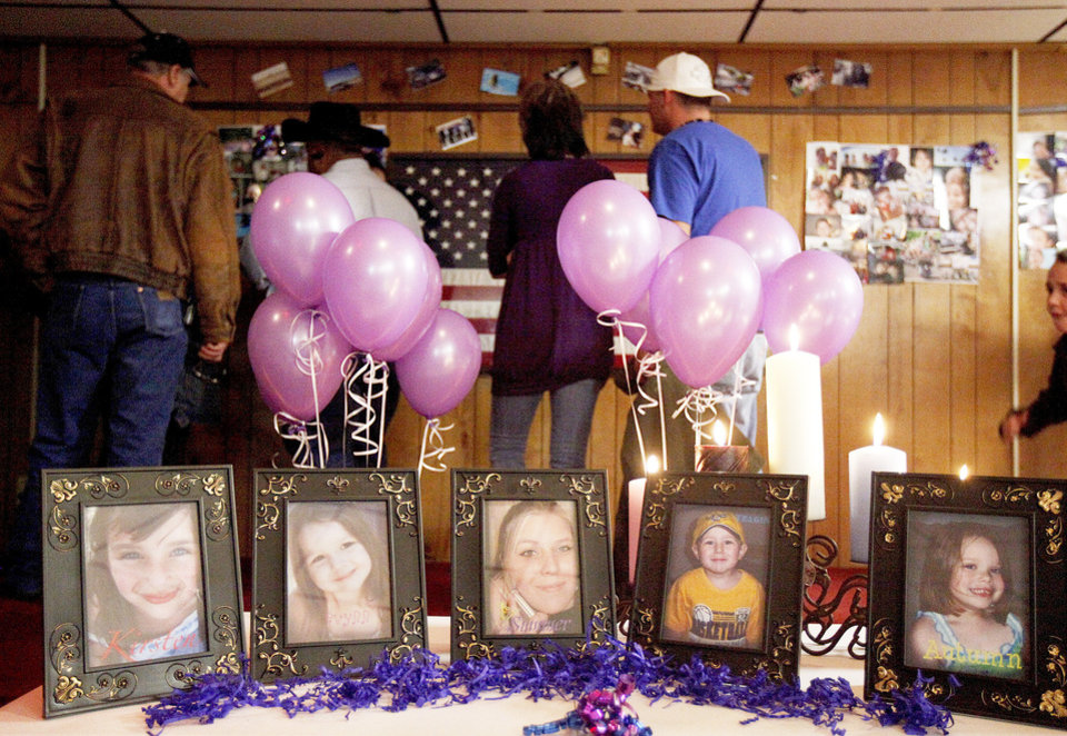 A crowd looks over pictures of Summer Rust and her four children during a vigil in El Reno on Tuesday. All five were slain one year ago in El Reno.  Photo by Bryan Terry, The Oklahoman