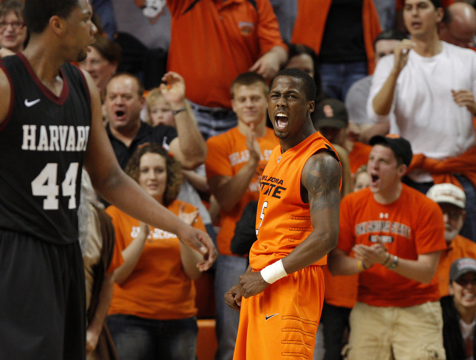 Photo - Oklahoma State's Reger Dowell (5) celebrates beside Harvard's Keith Wright (44) during a first-round NIT college basketball game between Oklahoma State University (OSU) and Harvard at Gallagher-Iba Arena in Stillwater, Okla., Tuesday, March 15, 2011. Photo by Bryan Terry, The Oklahoman