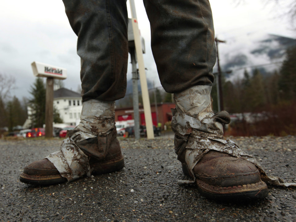 Photo - Sonny Blankenship, 18, a senior at Westin High School in Arlington, Wash.,. walks home from the Oso Fire Department after spending the day volunteering in the mudslide area, Tuesday, March 25, 2014, in Oso, Wash. Blankenship, who lives across the street from the Oso Fire Department, took the day off from school to sort through debris in the slide area just miles from his home. A massive mudslide struck near Arlington, on Saturday, killing at least 14 people over the weekend and leaving scores more missing. (AP Photo/The Herald, Mark Mulligan)