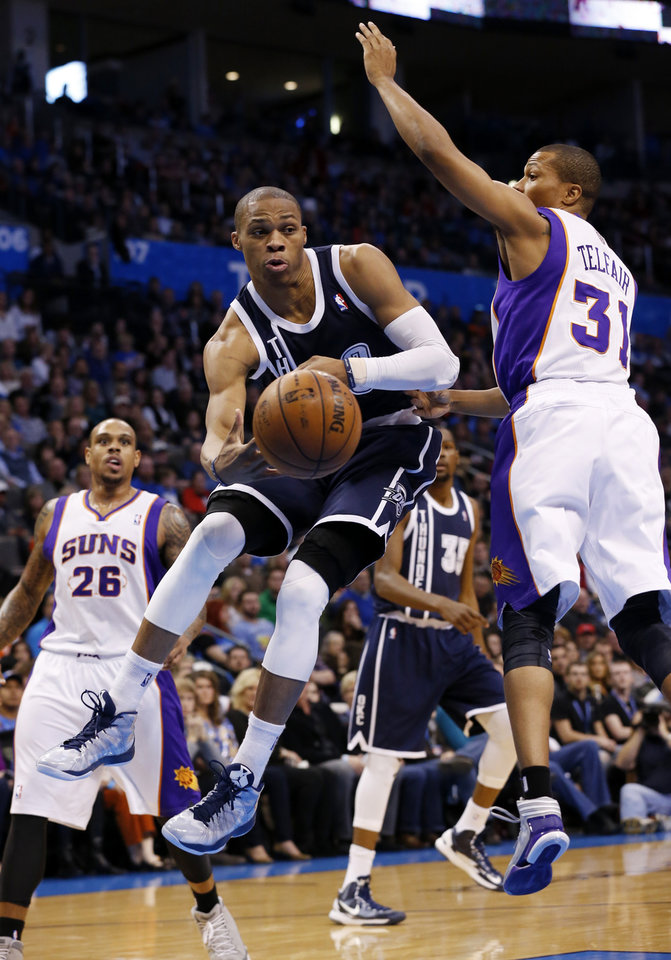 Photo - Oklahoma City Thunder's Russell Westbrook (0) passes around Phoenix Suns' Sebastian Telfair (31) as the Oklahoma City Thunder play the Phoenix Suns in NBA basketball at the Chesapeake Energy Arena in Oklahoma City, on Monday, Dec. 31, 2012.  Photo by Steve Sisney, The Oklahoman