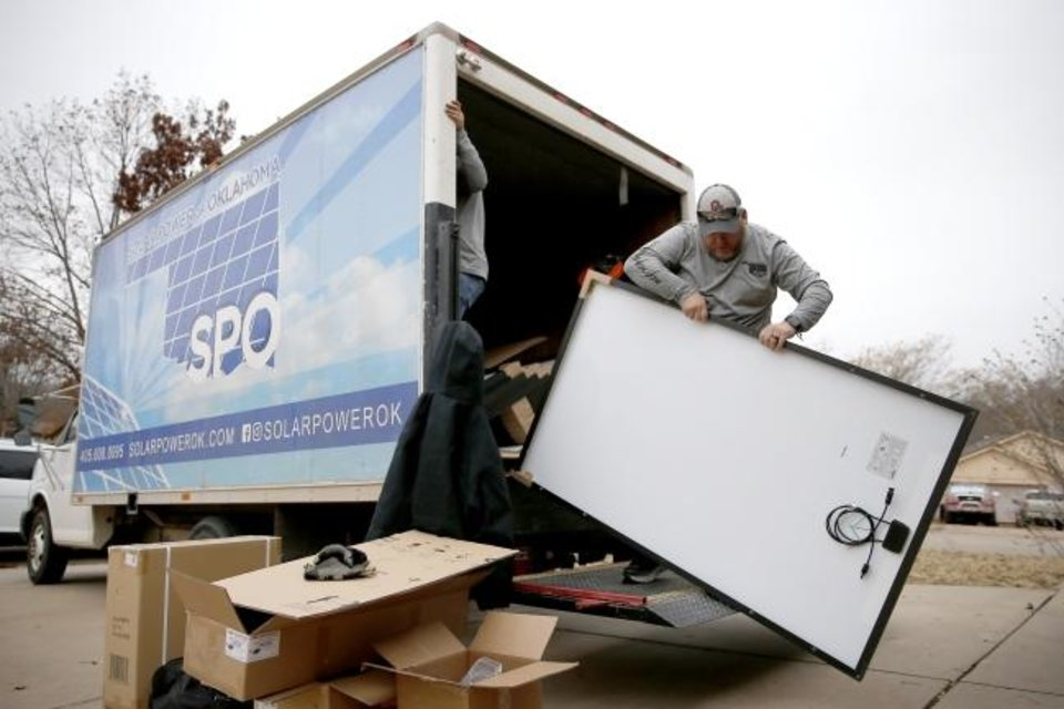 Photo -  Alex Lopez, with Solar Power of Oklahoma, unloads a solar panel. [BRYAN TERRY/THE OKLAHOMAN]