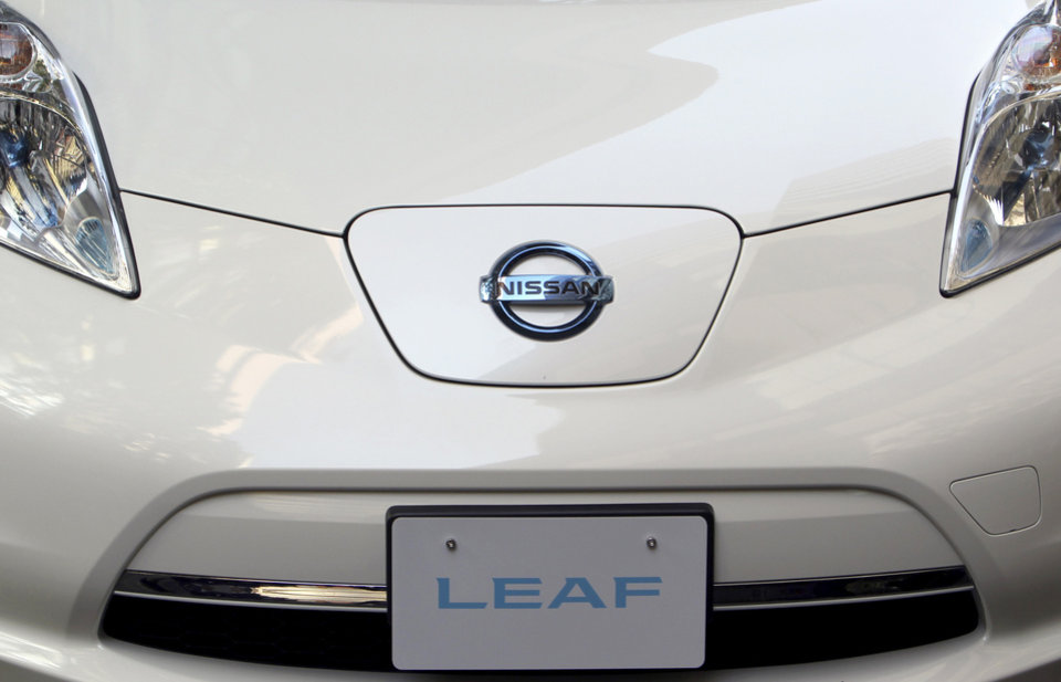 Nissan Motor Co.'s latest LEAF electric car is displayed for media in Tokyo, Tuesday, Nov. 20, 2012. The upgraded Leaf electric car from Nissan can travel further without recharging, comes in a cheaper model and tells drivers how much battery life is left. (AP Photo/Junji Kurokawa)