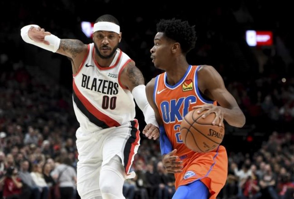 Photo -  Oklahoma City Thunder guard Shai Gilgeous-Alexander, right, drives to the basket on Portland Trail Blazers forward Carmelo Anthony during Sunday night's game in Portland. [AP Photo/Steve Dykes]