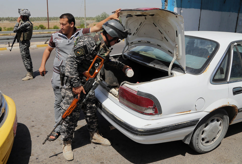 Photo - An Iraqi federal policeman stands guard as his colleague searches a car at a checkpoint in Baghdad, Iraq, Sunday, June 22, 2014. Sunni militants have seized another town in Iraq's western Anbar province, the fourth to fall in two days, officials said Sunday, in what is shaping up to be a major offensive in one of Iraq's most restive regions. (AP Photo/Karim Kadim)