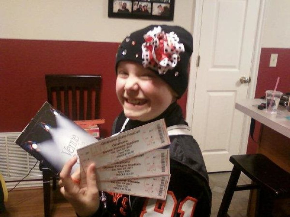 OSU fan Olivia Hamilton shows off her Bedlam tickets, which were provided by Scooter Procter, a Sooner fan who runs brokerage service OklahomaTickets.com.  PHOTO PROVIDED