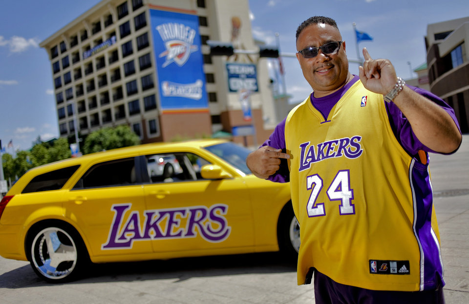 Photo - L.A. LAKERS: Los Angeles Lakers fan living in Oklahoma, Andre Mink poses for a photo with his Lakers painted car outside the Chesapeake Energy Arena on Thursday,  May 10, 2012, in Oklahoma City, Oklahoma. Photo by Chris Landsberger, The Oklahoman