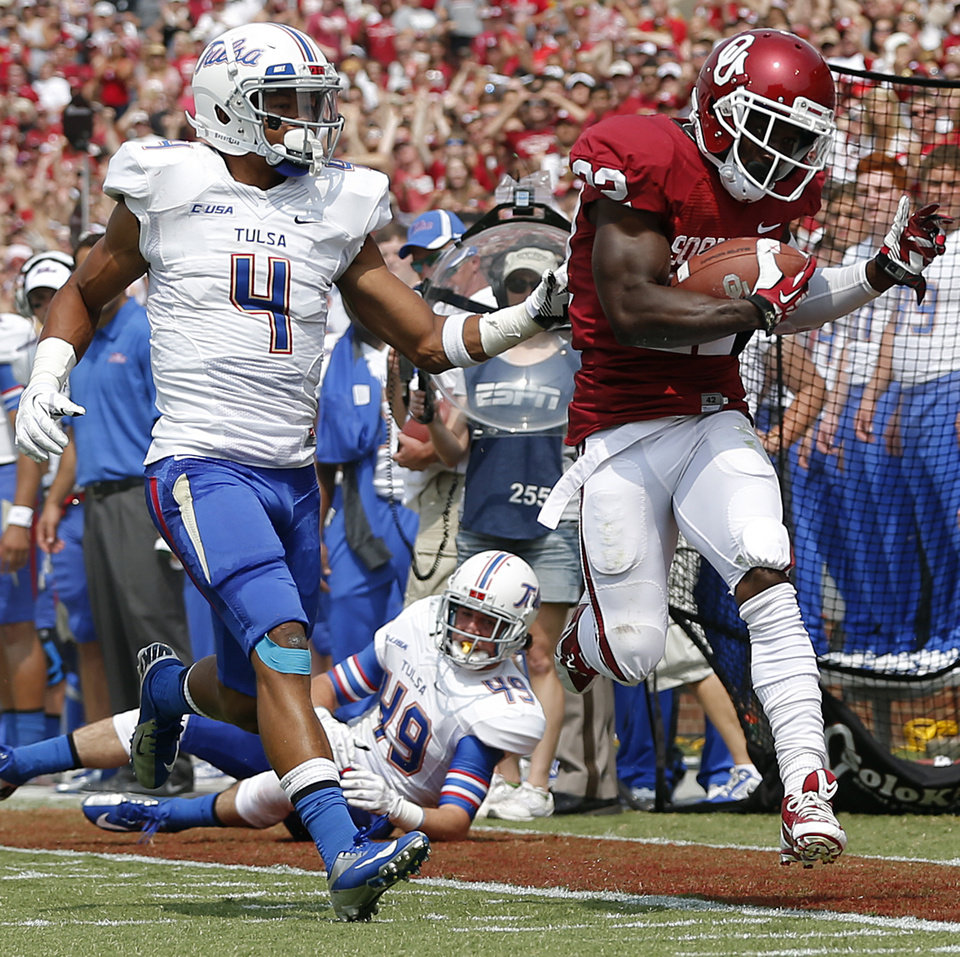 Photo - Oklahoma's Roy Finch (22) steps out of bounds in front of Tulsa 's Darnell Walker (4) during the college football game between the University of Oklahoma Sooners (OU) and the University of Tulsa Hurricanes (TU) at the Gaylord-Family Oklahoma Memorial Stadium on Saturday, Sept. 14, 2013 in Norman, Okla.  Photo by Chris Landsberger, The Oklahoman