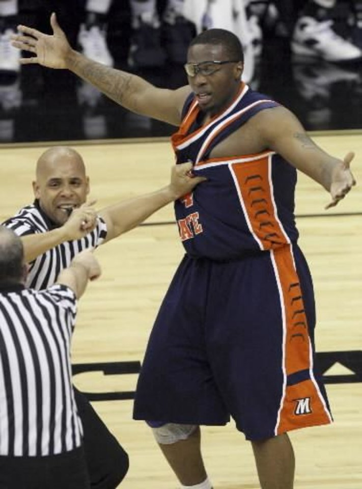 Photo - A referee grabs the jersey of Morgan State's  Ameer  Ali (34) after  Ali flipped Oklahoma's Blake Griffin over his back in the second half during a first-round men's NCAA college basketball tournament game in Kansas City, Mo., Thursday, March 19, 2009.  Ali was ejected from the game. (AP Photo/Ed Zurga)