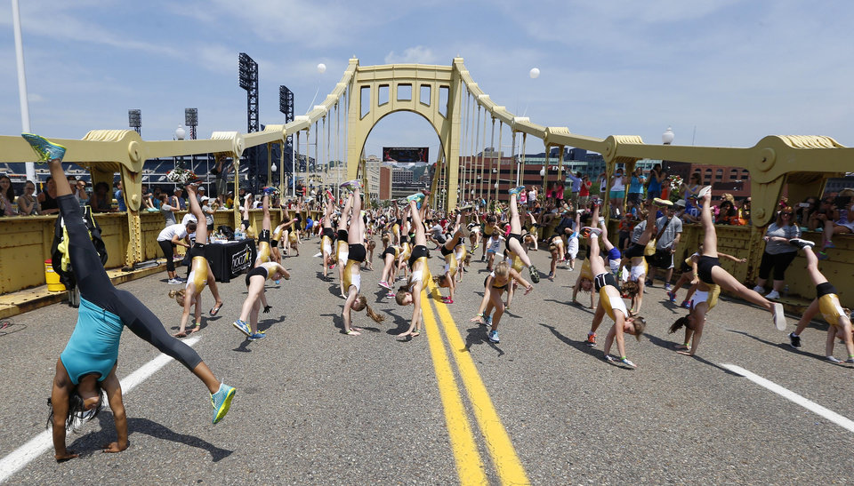 Photo - Olympic women's gymnastics champion Gabrielle Douglas, left, participates in a practice run in an effort to set a world record for most simultaneous cartwheels, Monday, June 23, 2014, in Pittsburgh. Douglas is hoping to return to competition at the USA Gymnastics national championships in Pittsburgh in August. (AP Photo/Keith Srakocic)