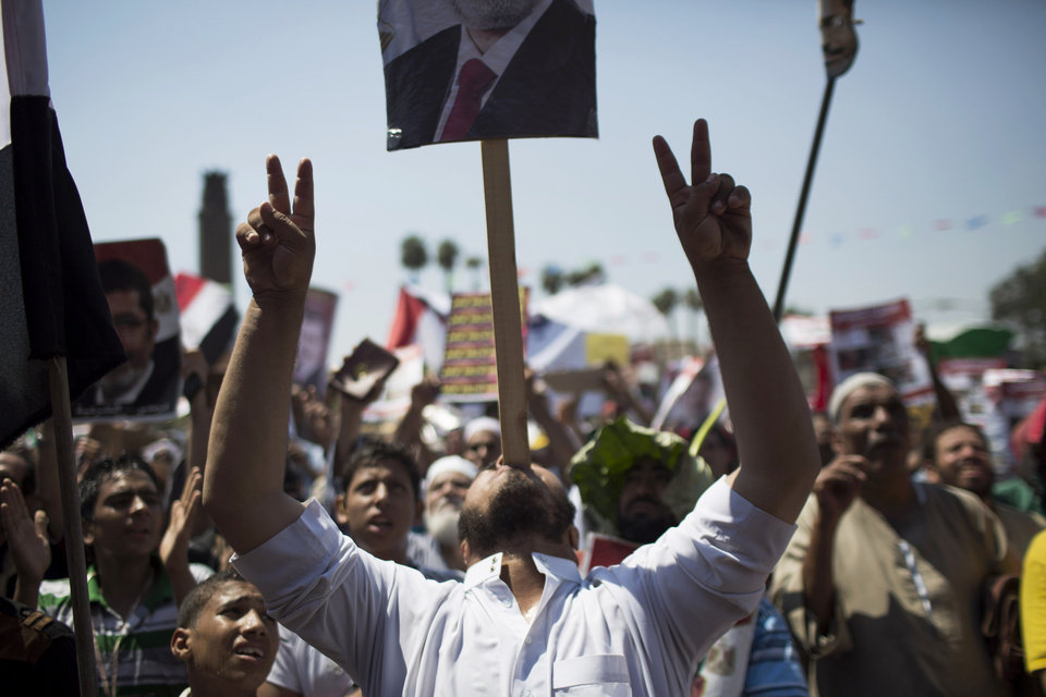 Photo - A supporter of Egypt's ousted President Mohammed Morsi makes the victory sign while holding a banner with his mouth during a protest near Cairo University in Giza, Cairo, Egypt, Friday, July 26, 2013. Egyptian prosecutors accused ousted President Mohammed Morsi on Friday of conspiring with the Palestinian militant group Hamas and murder in his 2011 escape from prison that left 14 guards dead. The development fueled the likelihood of clashes as tens of thousands of supporters and opponents of the Islamist leader massed for rival rallies. (AP Photo/Manu Brabo)