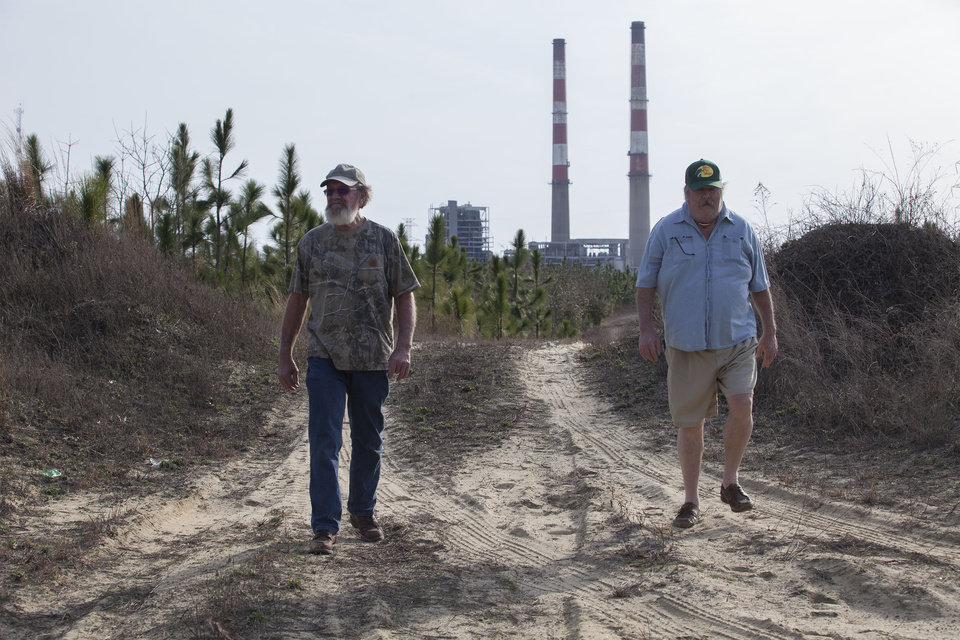 Photo - Flemington Road community neighbors Sam Malpass, left, and Kenneth Sandlin of Wilmington, N.C.,, walk through former hunting grounds near their homes on Wednesday, Feb. 19, 2014. The two are part of a small community near the L.V. Sutton Complex operated by Duke Energy they feel has polluted well water from spill off and seepage from large coal ash ponds.  The L.V. Sutton Complex operated by Duke Energy is in the background. (AP Photo/Randall Hill)