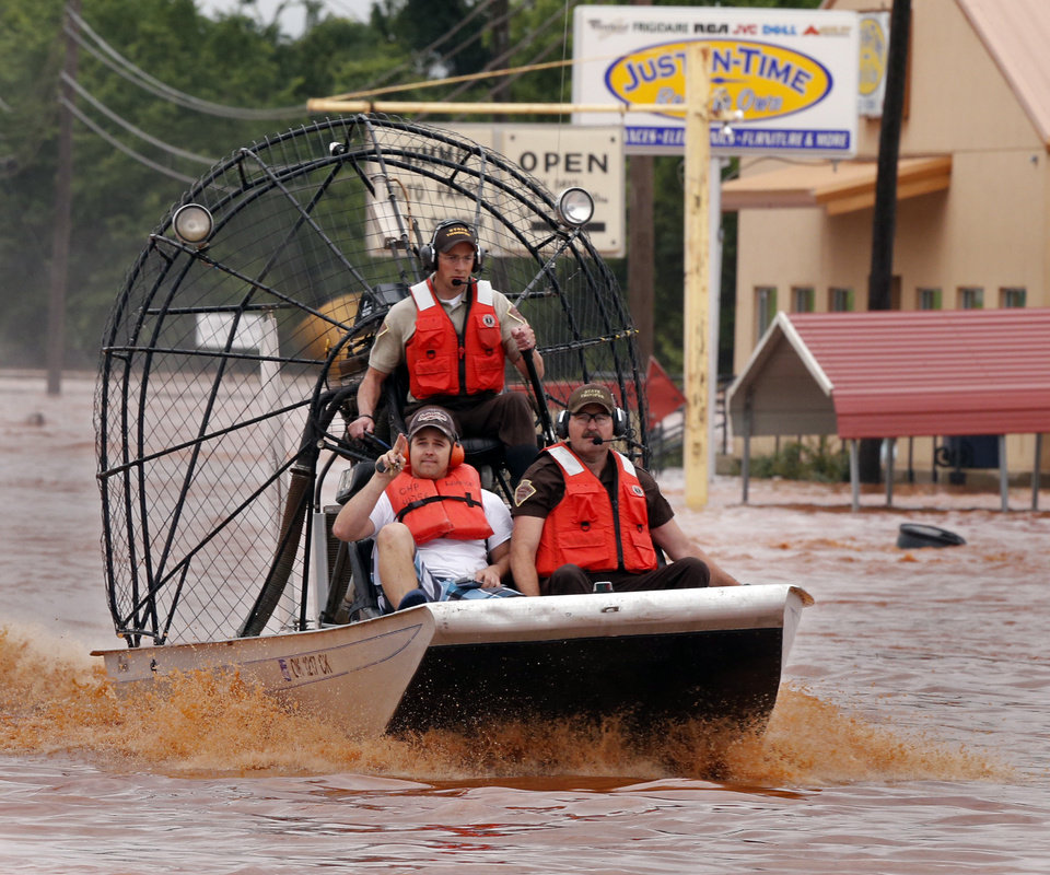 Photo - Highway patrolmen rescue Justin Nimmo from his business, Just-In-Time, after flooding caused by rising water from Saturday night's storms trapped him in the store on Sunday, May 24, 2015 in Purcell, Okla.  Photo by Steve Sisney The Oklahoman