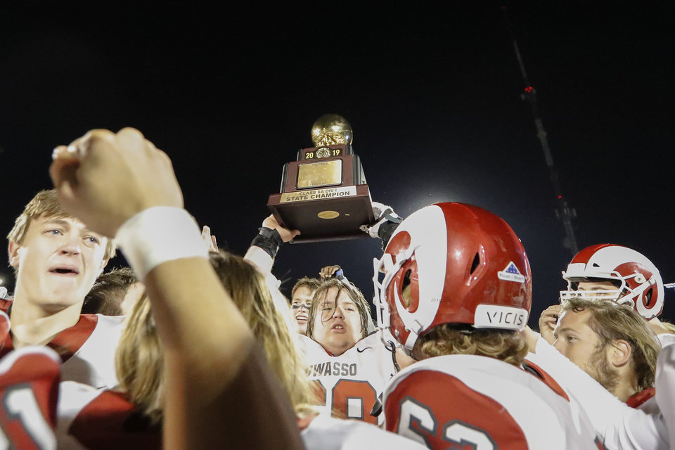 Photo - Owasso holds up the championship trophy after defeating Jenks in the OSSAA 6A-1 Championship game in Edmond, Okla., Saturday, Dec. 7, 2019. (Alonzo Adams for The Oklahoman)