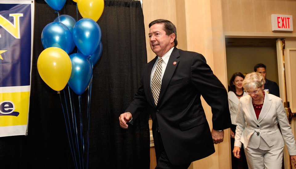 Photo - Drew Edmondson steps onto stage, followed by his wife, Linda, and family as he enters room to deliver his concession speech. Gubernatorial primary election watch party for Drew Edmondson at the Sheraton Hotel in downtown Oklahoma City, Tuesday, July 27, 2010.  Photo by Jim Beckel, The Oklahoman