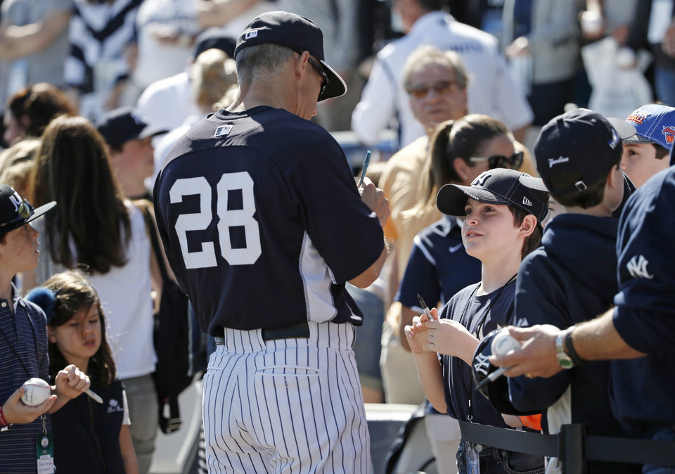 Photo - New York Yankees manager Joe Girardi (28) signs autographs for fans who were allowed to watch batting practice from the field before a spring exhibition baseball game against the Boston Red Sox in Tampa, Fla., Tuesday, March 18, 2014.  (AP Photo/Kathy Willens)
