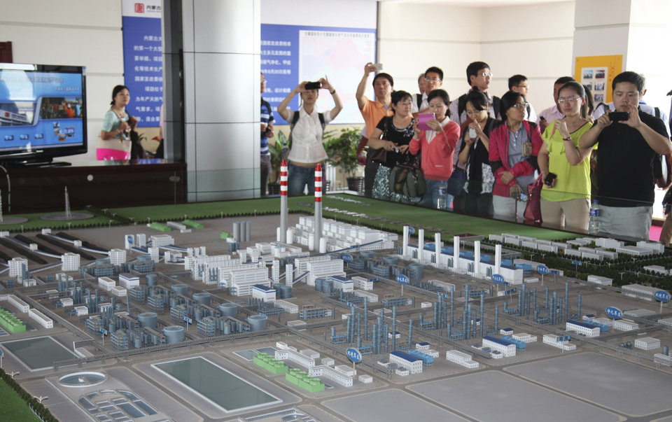 Photo - In this Friday, Aug. 8, 2014 photo, visitors to a state-of-the-art power plant that turns millions of tons of coal every year into methane, take photos of a scale model of the plant in northern China's Inner Mongolia province. Chinese leaders are under intense pressure to meet rising energy needs spurred by economic growth but are hampered by insufficient reserves of natural gas and oil. At the same time, China's massive cities are contending with air pollution so intense it can shut down schools and airports and, studies show, shorten life expectancy by as many as five years. (AP Photo/Jack Chang)