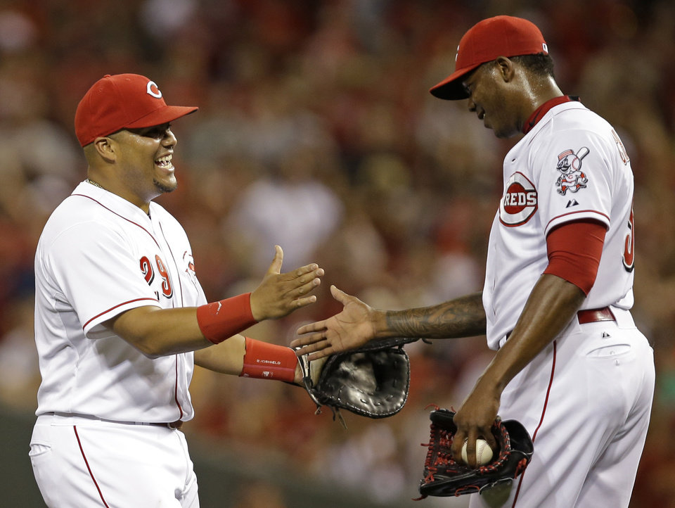 Photo - Cincinnati Reds' Brayan Pena, left, congratulates relief pitcher Aroldis Chapman after they defeated the Pittsburgh Pirates 6-5 in a baseball game, Friday, July 11, 2014, in Cincinnati. Pena drove in the winning run in the eighth inning and Chapman struck out the side in the ninth inning to earn his 20th save. (AP Photo/Al Behrman)