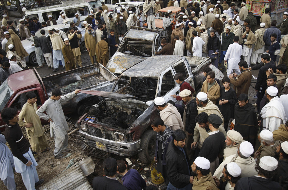 Photo - People look at damaged vehicles after a  bomb blast in the Pakistani tribal area of Khyber, Monday, Dec. 17, 2012. A car bomb exploded outside the women's waiting area of a government office in Pakistan's troubled northwest tribal region, killing many  people and wounding others, government officials said. (AP Photo/Mohammed Sajjad)