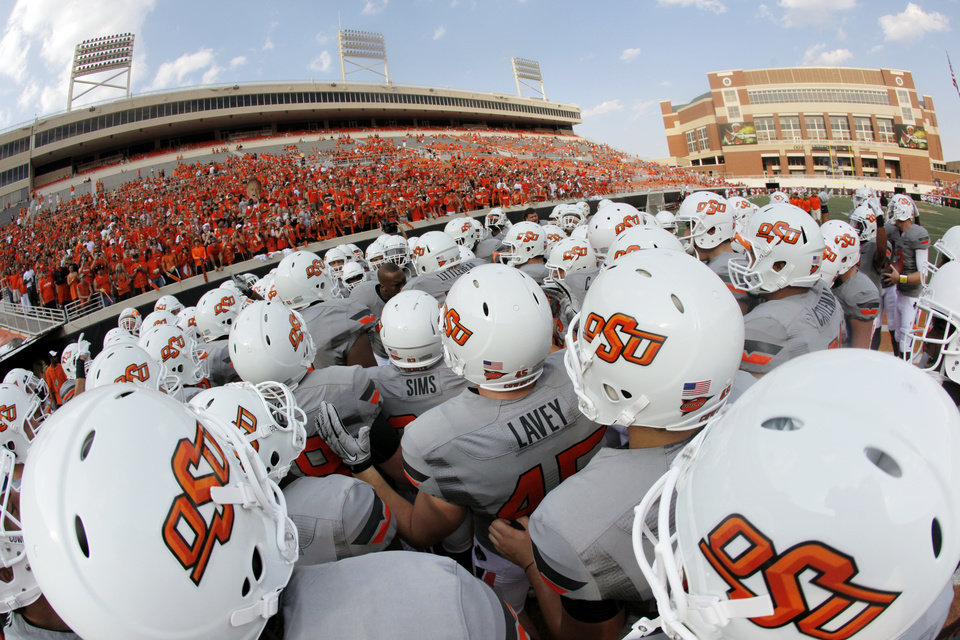 Photo - The OSU football team gathers before its game vs. La.-Lafayette in Stillwater on Saturday. The Cowboys were wearing their new uniforms for the first time. Photo by Nate Billings, The Oklahoman