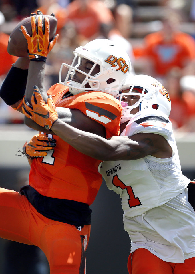 Photo - OSU's Jhajuan Seales (81) makes a catch as he is tackled by Kevin Peterson (1) during the Oklahoma State University Spring football game at Boone Pickens Stadium in Stillwater, Okla., Saturday, April, 18, 2015. Photo by Sarah Phipps, The Oklahoman
