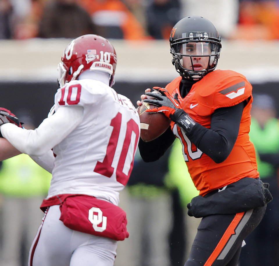 Photo - Oklahoma State's Clint Chelf (10) looks to pass the ball past Oklahoma's Quentin Hayes (10) during the Bedlam college football game between the Oklahoma State University Cowboys (OSU) and the University of Oklahoma Sooners (OU) at Boone Pickens Stadium in Stillwater, Okla., Saturday, Dec. 7, 2013. Photo by Chris Landsberger, The Oklahoman