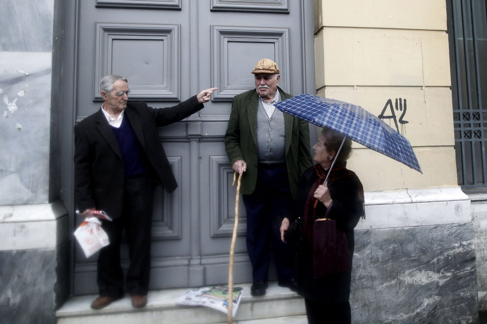 Athenians chat outside a bank as they shelter from a rainfall in central Athens, Tuesday, Dec. 18, 2012. Greece is failing to collect the tax it is owed and is in danger of missing key targets that need to be met to reduce the government\'s staggering debt pile, the European Union warned on Monday. (AP Photo/Petros Giannakouris)