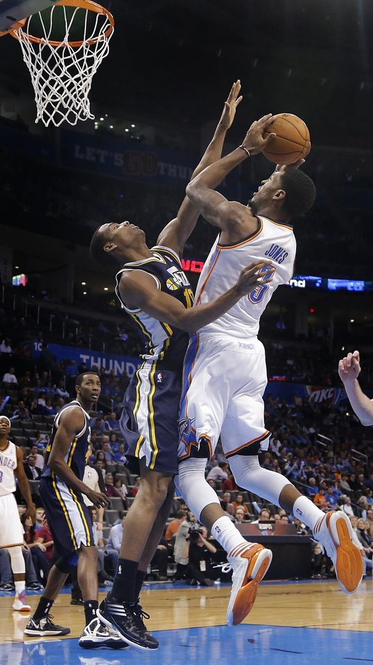 Photo - Oklahoma City Thunder's Perry Jones (3) is fouled by Utah Jazz's Alec Burks (10) as he goes up for a shot during the NBA basketball game between the Oklahoma City Thunder and the Utah Jazz at Chesapeake Energy Arena on Wednesday, March 13, 2013, in Oklahoma City, Okla. Photo by Chris Landsberger, The Oklahoman