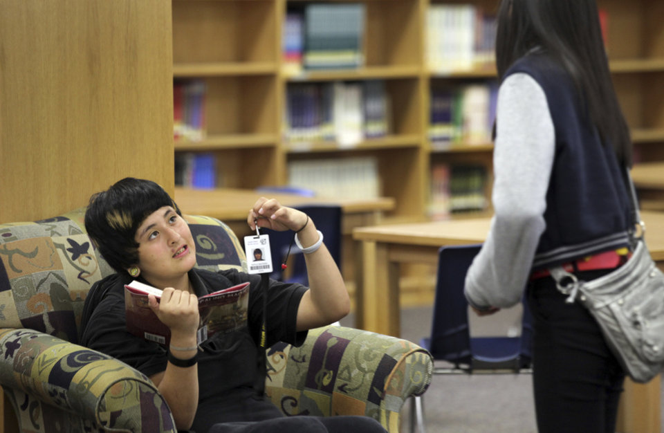"In this Oct. 1, 2012 photo, Kayla Saucedo, left, shows her ID badge to a fellow student at Anson Jones Middle School in San Antonio, Texas. The San Antonio school district's website was hacked over the weekend to protest its policy requiring students to wear microchip-embedded cards tracking their every move on campus. A teenager purportedly working with the hacker group Anonymous said in an online statement that he took the site down because the Northside school district ""is stripping away the privacy of students in your school."" All students at John Jay High School and Anson Jones Middle School are required to carry identification cards embedded with a microchip. They are tracked by the dozens of electronic readers installed in the schools' ceiling panels. (AP Photo/San Antonio Express-News, Bob Owen) RUMBO DE SAN ANTONIO OUT; NO SALES"